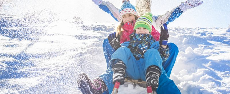 Happy family having fun together on the snowy mountain, on a sled.
